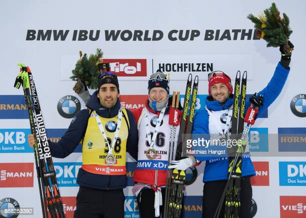Martin Fourcade of France celebrates second place Johannes Thingnes Boe of Norway celebrates first place and Jakov Fak of Slovenia celebrates third...