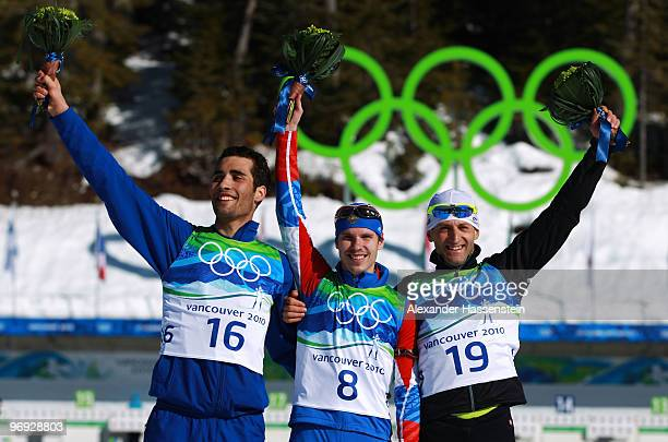 Martin Fourcade of France celebrates winning silver Evgeny Ustyugov of Russia gold and Pavol Hurajt of Slovakia bronze during the flower ceremony for...