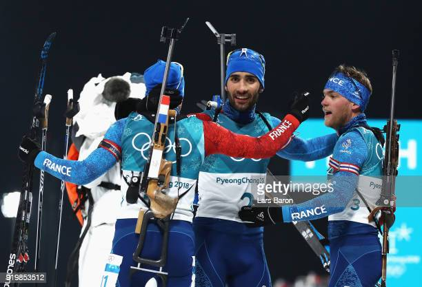 Martin Fourcade of France celebrates winning the gold medal with Simon Desthieux of France and Antonin Guigonnat of France during the Men's 15km Mass...