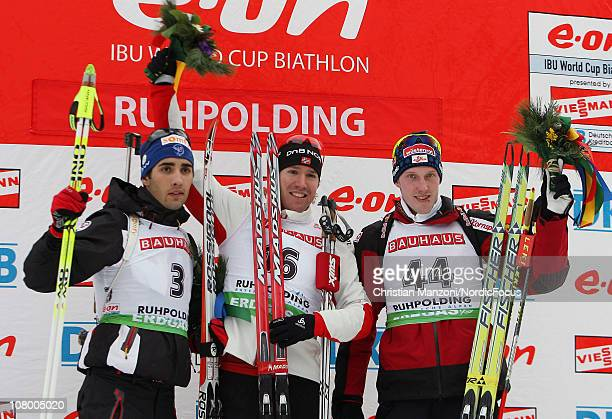 Martin Fourcade of France celebrates with Emil Hegle Svendsen of Norway and Dominik Landertinger of Austria after the men's individual during the EON...