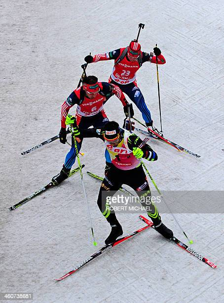 Martin Fourcade of France competes in front of Anton Shipulin of Russia and Alexander Loginov of Russia during the men's 15 km mass start event of...