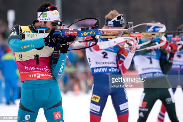Martin Fourcade of France Johannes Thingnes Boe of Norway and Simon Schempp of Germany at the shooting range during the men's mass start event of the...