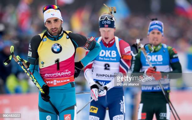 Martin Fourcade of France Johannes Thingnes Boe of Norway and Simon Schempp of Germany arrive at the shooting range during the men's mass start event...