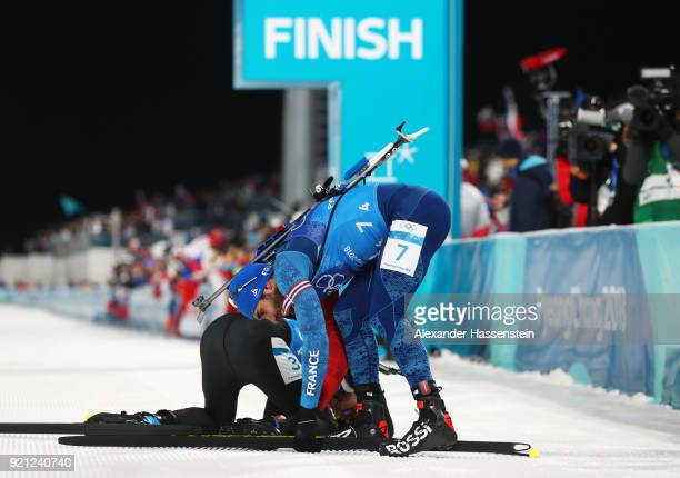 Martin Fourcade of France removes his skis after winning the gold medal as Arnd Peiffer of Germany reacts to placing fourth during the Biathlon 2x6km...