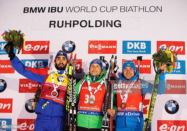 Martin Fourcade of France second place Erik Lesser of Germany first place and Evgeniy Garanichev of Russia third place celebrate on the podium after...