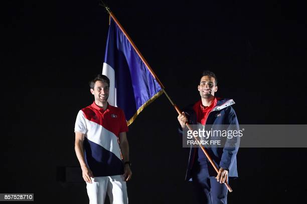 Martin Fourcade twotime Olympic biathlon champion and flagbearer of the French team at the Pyeongchang Winter Games in February 2018 flanked by Jason...