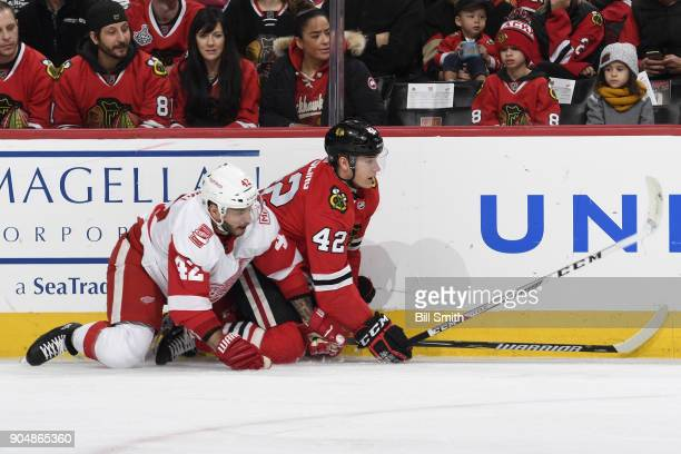 Martin Frk of the Detroit Red Wings and Gustav Forsling of the Chicago Blackhawks watch for the puck after falling to the ice in the first period at...