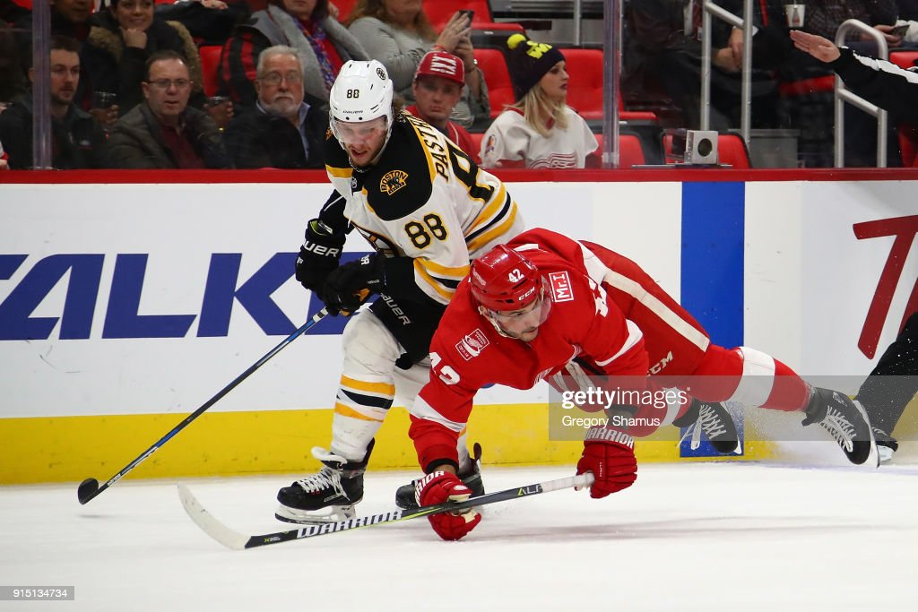 Martin Frk #42 of the Detroit Red Wings losses his footing next to David Pastrnak #88 of the Boston Bruins during the third period at Little Caesars Arena on February 6, 2018 in Detroit, Michigan. Boston won the game 3-2.