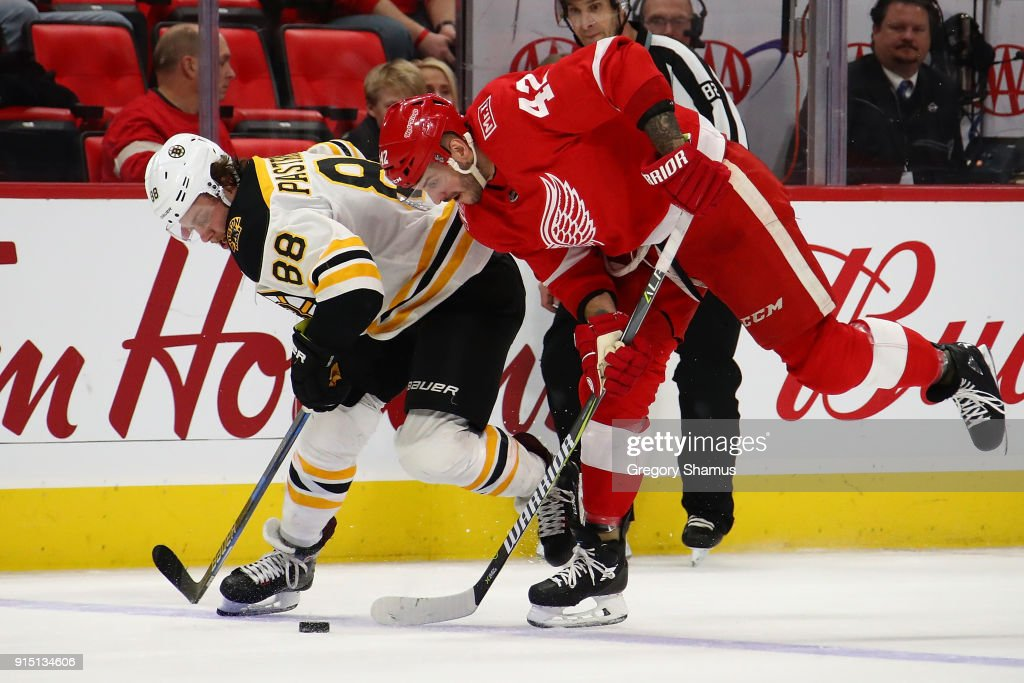 Martin Frk #42 of the Detroit Red Wings tries tries to get control of the puck next to David Pastrnak #88 of the Boston Bruins during the third period at Little Caesars Arena on February 6, 2018 in Detroit, Michigan. Boston won the game 3-2.