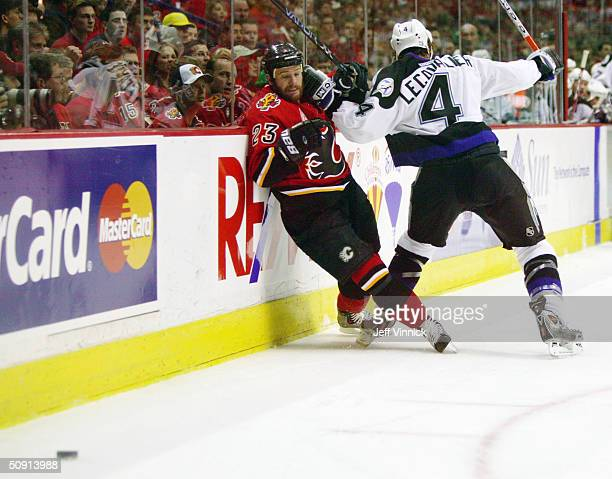 Martin Gelinas of the Calgary Flames is pinned-up against the boards by Vincent Lecavalier of the Tampa Bay Lightning during the first period in game...