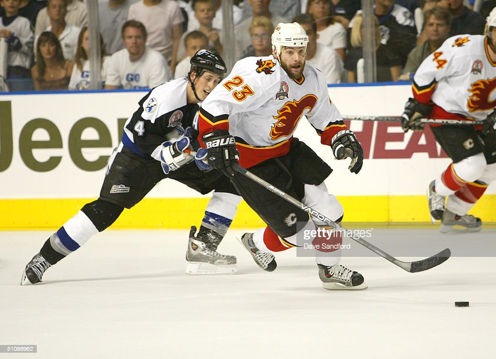 Martin Gelinas #23 of the Calgary Flames skates for the puck against Vincent Lecavalier #4 of the Tampa Bay Lightning in Game seven of the NHL Stanley Cup Finals on June 7, 2004 at the St. Pete Times Forum in Tampa, Florida. The Lightning defeated the Flames 2-1.