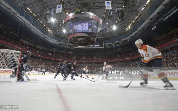 Martin Gelinas of the Florida Panthers carries the puck as Rory Fitzpatrick and Roberto Luongo of the Vancouver Canucks look on during their game...