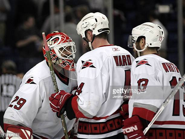 Martin Gerber of the Carolina Hurricanes is congratulated on his shut out by teammates Aaron Ward and Ray Whitney during game 4 of the Eastern...