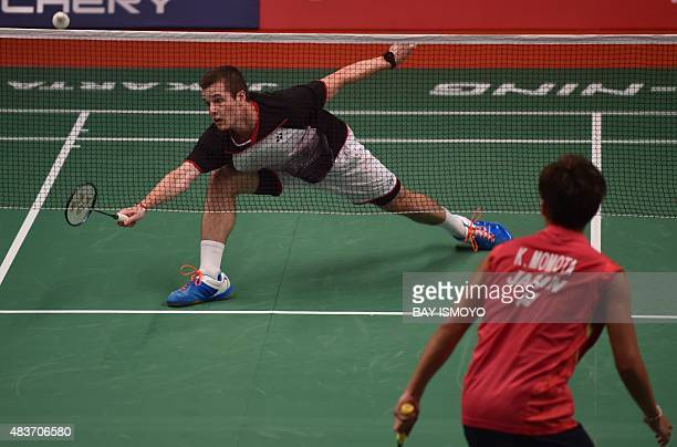 Martin Giuffre of Canada hits a return against Kento Momota of Japan during their men's singles qualifying match at the 2015 World Championships...