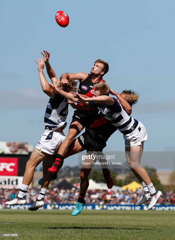 Martin Gleeson (top) and Darcy Parish of the Bombers compete for the ball with Cameron Guthrie (left) and Zach Guthrie of the Cats during the AFL 2018 JLT Community Series match between the Geelong Cats and the Essendon Bombers at Central Reserve on March 11, 2018 in Colac, Australia.