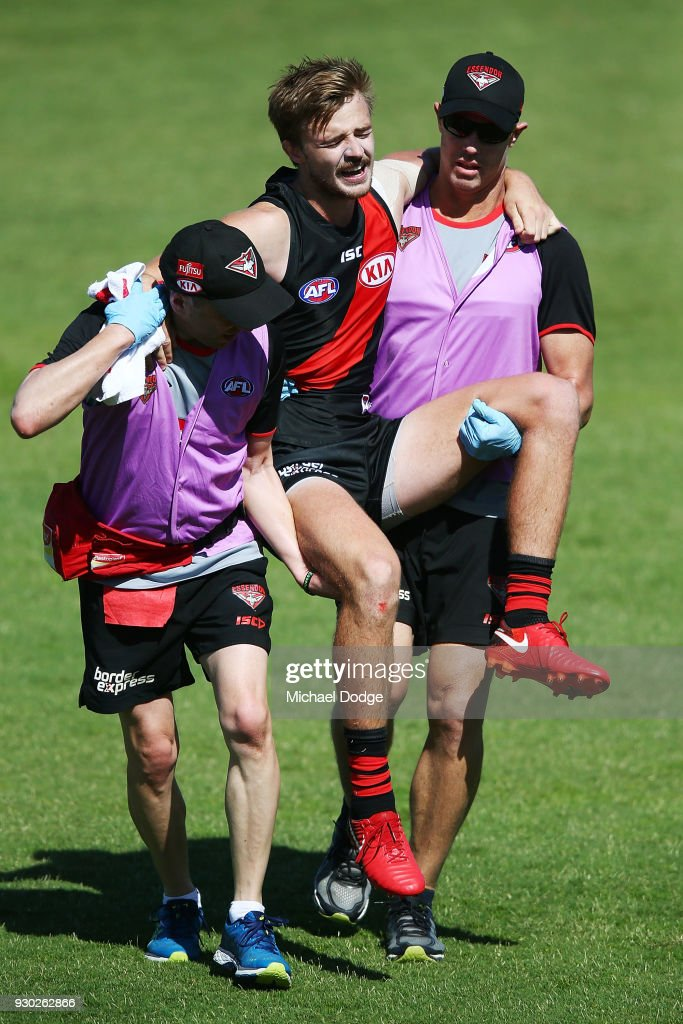 Martin Gleeson of the Bombers is carried off after sustaining a leg injury when landing in a contest for the ball against Cameron Guthrie of the Cats during the JLT Community Series AFL match between the Geelong Cats and the Essendon Bombers at Central Reserve on March 11, 2018 in Colac, Australia.