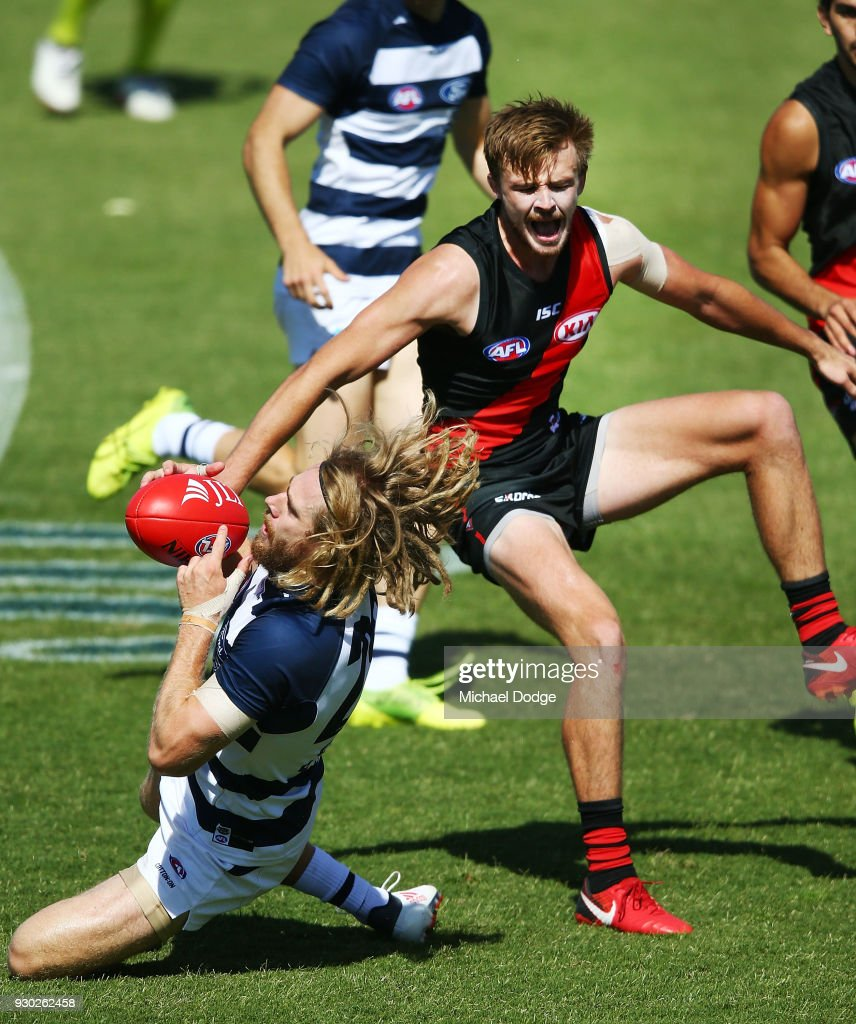Martin Gleeson of the Bombers sustains a leg injury when landing in this contest for the ball against Cameron Guthrie of the Cats during the JLT Community Series AFL match between the Geelong Cats and the Essendon Bombers at Central Reserve on March 11, 2018 in Colac, Australia.