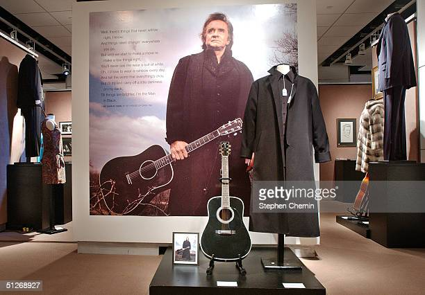 Martin guitar and a poster of him wearing the coat and holding the guitar along with other memorabilia belonging to country singing legends Johnny...