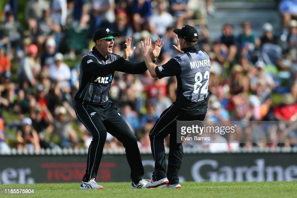 Martin Guptill and Colin Munro celebrate a wicket during game three of the Twenty20 International series between New Zealand and England at Saxton...