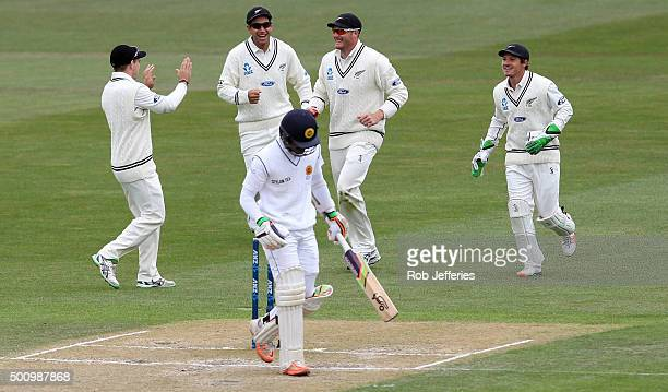 Martin Guptill of New Zealand celebrates taking a catch with Tom Latham, Ross Taylor and BJ Watling to dismiss Dinesh Chandimal of Sri Lanka during...