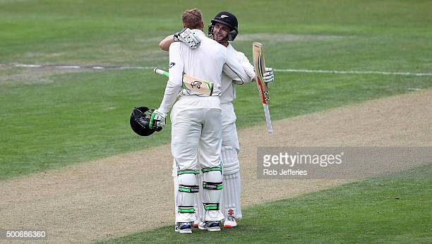 Martin Guptill of New Zealand celebrates with Kane Williamson after scoring 100 runs during day one of the First Test match between New Zealand and...