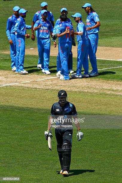 Martin Guptill of New Zealand leaves the field after being dismissed while Indian players celebrate during the first One Day International match...