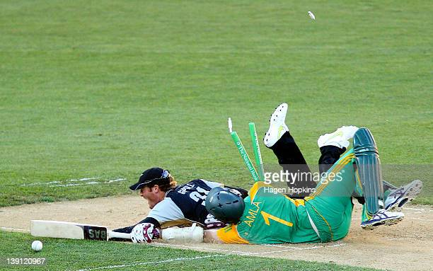 Martin Guptill of New Zealand runs out Hashim Alma of South Africa during the first International Twenty20 match between New Zealand and South Africa...