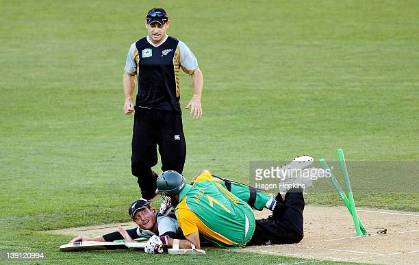 Martin Guptill of New Zealand runs out Hashim Alma of South Africa while teammate Nathan McCullum looks on during the first International Twenty20...