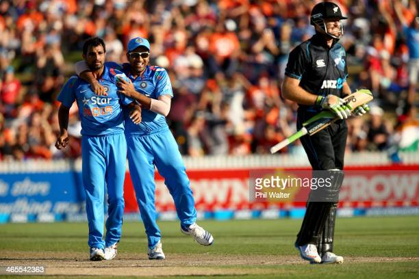 Martin Guptill of New Zealand walks off as Mohammed Shami and Rohit Sharma of India celebrate his dismissal during game four of the men's one day...