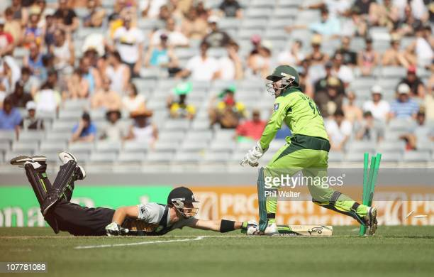 Martin Guptill of the Blackcaps is run out by Mohammad Hafeez as wicketkeeper Umar Akmal of Pakistan celebrates during game one of the Twenty20...