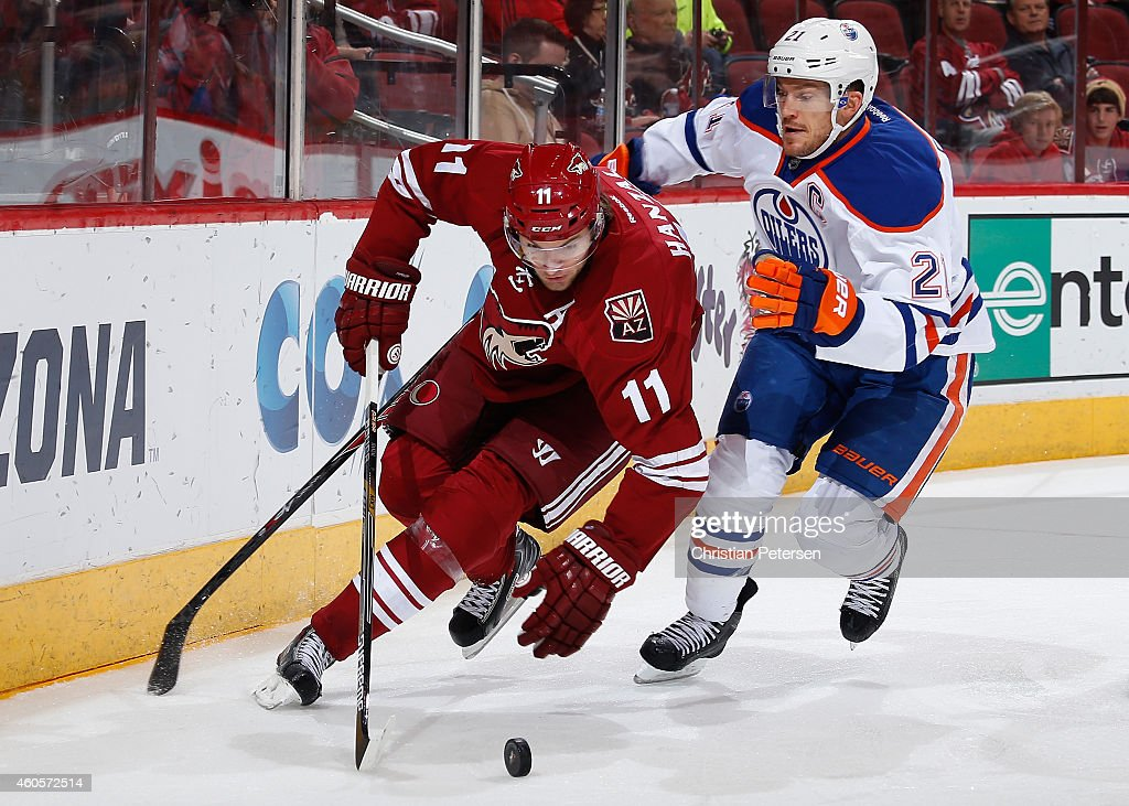 Martin Hanzal #11 of the Arizona Coyotes skates with the puck past Andrew Ference #21 of the Edmonton Oilers during the first period of the NHL game at Gila River Arena on December 16, 2014 in Glendale, Arizona.