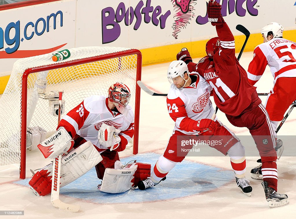 Martin Hanzal #11 of the Phoenix Coyotes gets tied up with Ruslan Salei #24 of the Detroit Red Wings in front of Red Wings goaltender Jimmy Howard #35 on April 18, 2011 in Game Three of the Western Conference Quarterfinals during the 2011 NHL Stanley Cup Playoffs at Jobing.com Arena in Glendale, Arizona.