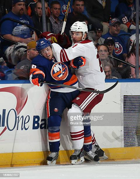 Martin Hanzal of the Phoenix Coyotes hits PierreMarc Bouchard of the New York Islanders during the first period at the Nassau Veterans Memorial...
