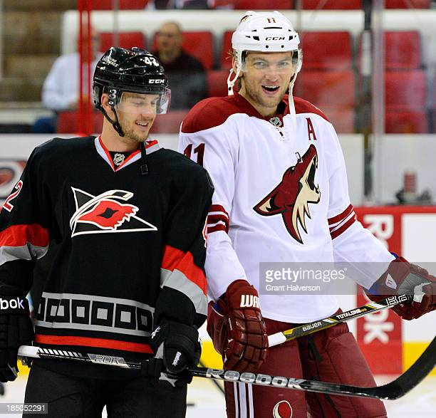 Martin Hanzal of the Phoenix Coyotes jokes with Brett Sutter of the Carolina Hurricanes before play at PNC Arena on October 13, 2013 in Raleigh,...
