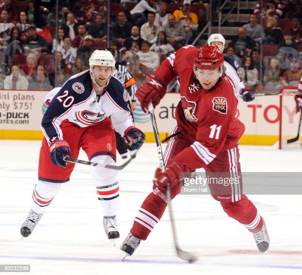 Martin Hanzal of the Phoenix Coyotes passes the puck as Kristian Huselius of the Columbus Blue Jackets skates up behind him during second period play...