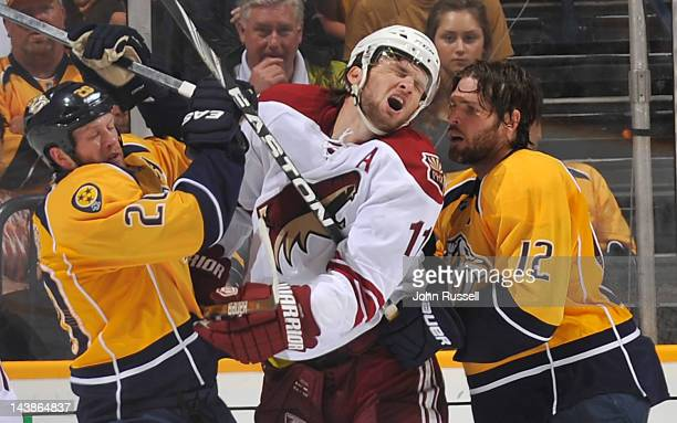 Martin Hanzal of the Phoenix Coyotes takes a shot to the face from Ryan Suter of the Nashville Predators in Game Four of the Western Conference...