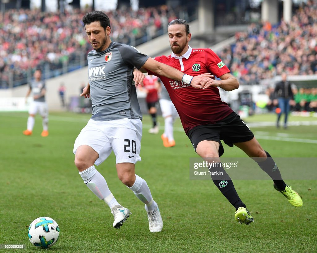 Martin Harnik of Hannover is challenged by Gojko Kacar of Augsburg during the Bundesliga match between Hannover 96 and FC Augsburg at HDI-Arena on March 10, 2018 in Hanover, Germany.