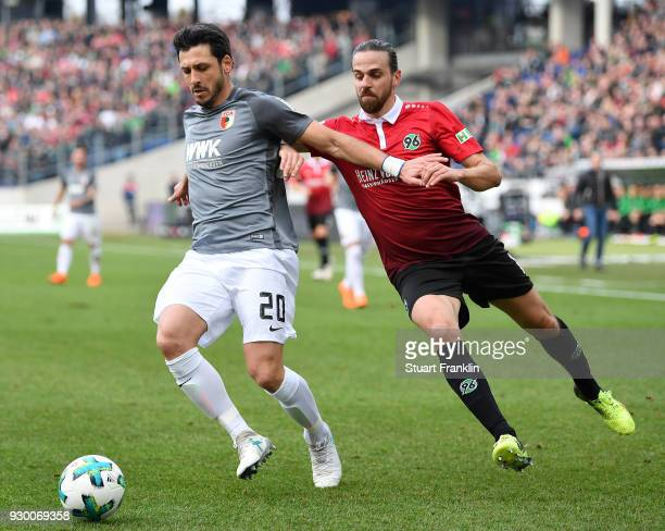 Martin Harnik of Hannover is challenged by Gojko Kacar of Augsburg during the Bundesliga match between Hannover 96 and FC Augsburg at HDIArena on...