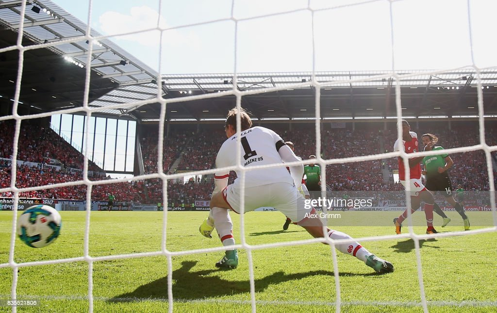 Martin Harnik (R) of Hannover scores his team's first goal past goalkeeper Rene Adler of Mainz during the Bundesliga match between 1. FSV Mainz 05 and Hannover 96 at Opel Arena on August 19, 2017 in Mainz, Germany.