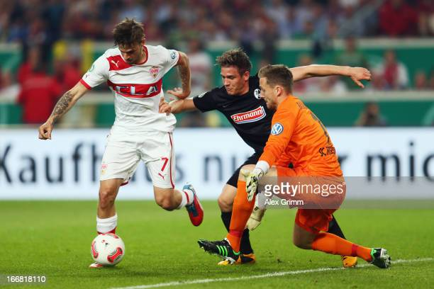 Martin Harnik of Stuttgart tries to score against Oliver Sorg and goalkeeper Oliver Baumann of Freiburg during the DFB Cup Semi Final match between...