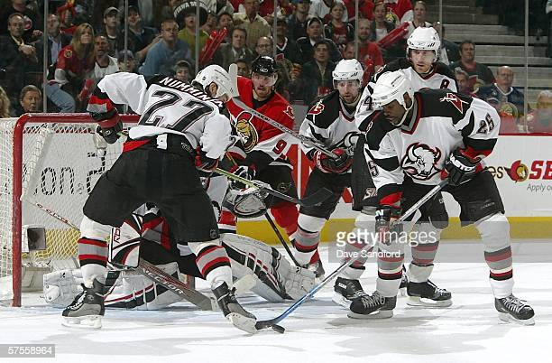 Martin Havlat of the Ottawa Senators keeps his eye on the puck after Ryan Miller of the Buffalo Sabres makes a save and Mike Grier clears the puck as...