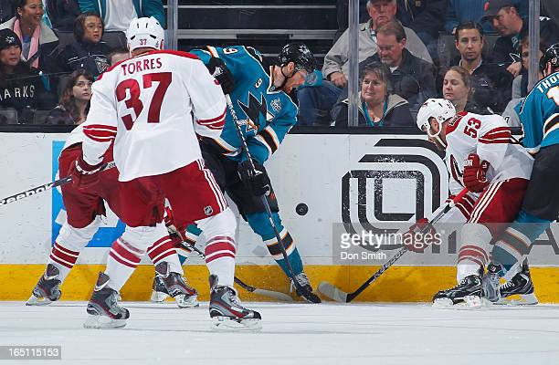 Martin Havlat of the San Jose Sharks fights for the puck against Derek Morris and Raffi Torres of the Phoenix Coyotes during an NHL game on March 30...