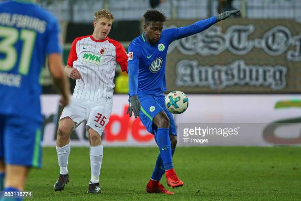Martin Hinteregger of Augsburg and Divock Origi of Wolfsburg battle for the ball during the Bundesliga match between FC Augsburg and VfL Wolfsburg at...