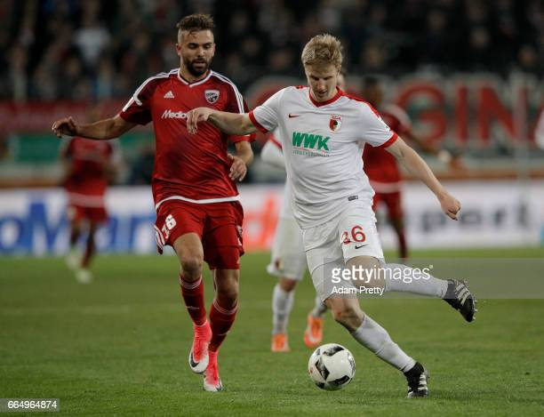 Martin Hinteregger of Augsburg and Lukas Hinterseer of Ingolstadt battle for the ball during the Bundesliga match between FC Augsburg and FC...