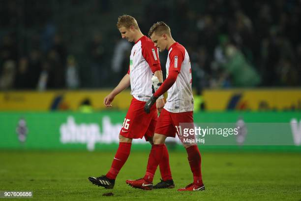 Martin Hinteregger of Augsburg and Philipp Max of Augsburg leave the pitch dejected after the Bundesliga match between Borussia Moenchengladbach and...
