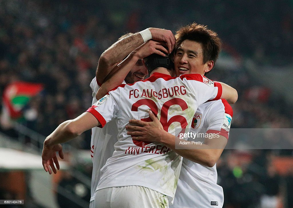 Martin Hinteregger of Augsburg celebrates with Koo Ja-Cheol after scoring a goal during the Bundesliga match between FC Augsburg and Borussia Moenchengladbach at WWK Arena on December 17, 2016 in Augsburg, Germany.