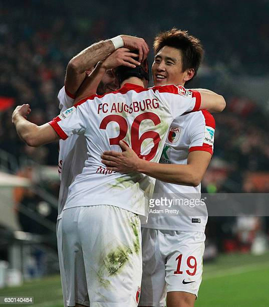 Martin Hinteregger of Augsburg celebrates with Koo JaCheol after scoring a goal during the Bundesliga match between FC Augsburg and Borussia...