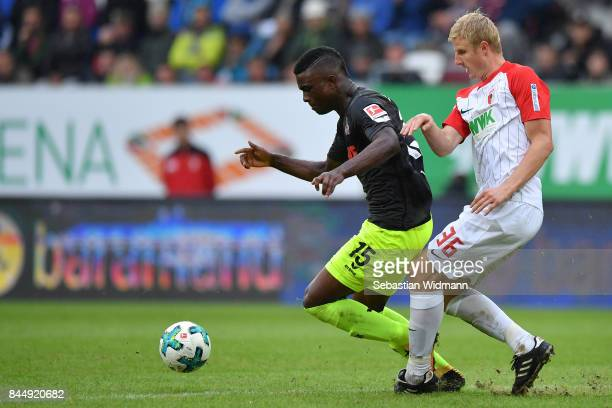 Martin Hinteregger of Augsburg challenges Jhon Cordoba of Koeln during the Bundesliga match between FC Augsburg and 1 FC Koeln at WWKArena on...