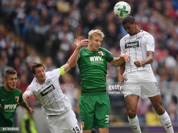 Martin Hinteregger of Augsburg jumps for a header with Sebastien Haller of Frankfurt during the Bundesliga match between Eintracht Frankfurt and FC...