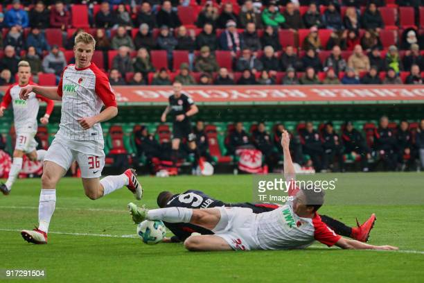 Martin Hinteregger of Augsburg Raphael Framberger of Augsburg and Sebastien Haller of Frankfurt battle for the ball during the Bundesliga match...